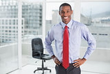 Elegant smiling Afro businessman standing in office