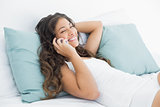 Happy woman using mobile phone in bed