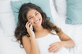 Smiling young woman using mobile phone in bed