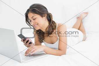 Casual woman using laptop while text messaging in bed