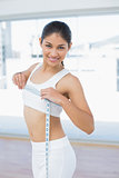 Smiling woman measuring chest in fitness studio