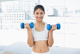 Woman exercising with dumbbells in fitness studio
