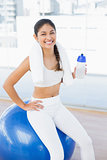 Woman on exercise ball with water bottle in fitness studio