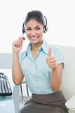 Businesswoman wearing headset while gesturing thumbs up
