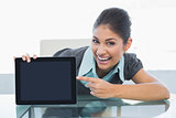 Portrait of smiling businesswoman displaying tablet PC