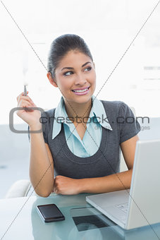 Thoughtful businesswoman using laptop in office