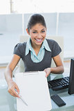 Smiling businesswoman with clipboard at office desk