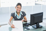 Businesswoman with clipboard sitting at office
