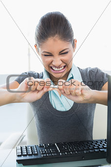 Angry businesswoman breaking pen over computer keyboard