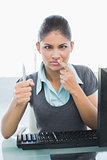Confused businesswoman with pen at office desk