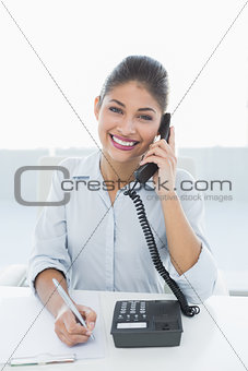 Portrait of an elegant businesswoman using telephone at desk