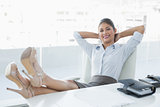 Relaxed businesswoman sitting with legs on desk in office