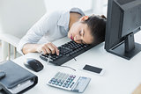 Businesswoman resting head on keyboard in office