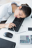 Vusinesswoman resting head on keyboard in office