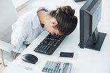 Businesswoman resting head on keyboard in office