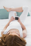 Relaxed woman looking at mobile phone in bed