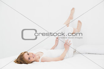 Full length portrait of a smiling woman lying in bed