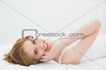 Portrait of a relaxed woman using mobile phone in bed