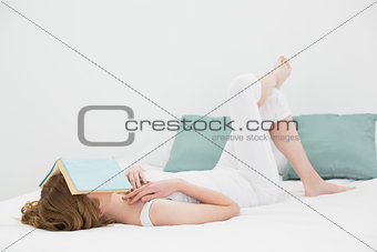 Woman with book over face resting in bed
