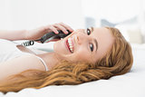 Relaxed young woman using telephone in bed