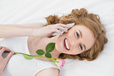 Woman using mobile phone while resting in bed with rose