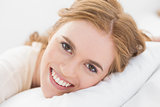 Close up of pretty young woman resting in bed