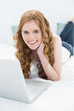 Portrait of smiling casual blond with laptop in bed