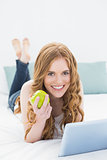 Casual blond using tablet PC while holding an apple in bed