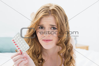 Close up portrait of worried blond with pills