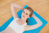 Sporty fit woman doing sit ups in fitness studio