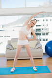 Sporty woman stretching body in fitness center