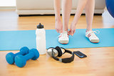 Female tying shoes with sporty equipment in fitness center