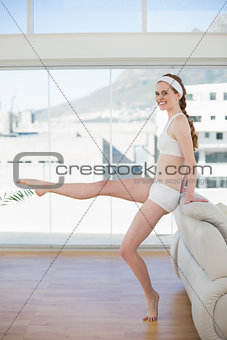 Toned woman stretching leg in fitness center