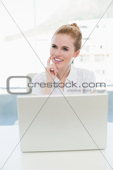 Thoughtful businesswoman with laptop in office