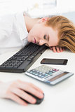 Businesswoman resting head on keyboard