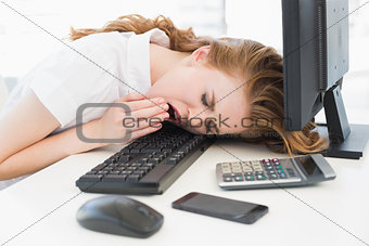 Asleep businesswoman yawning on keyboard at office
