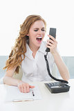Businesswoman shouting into the phone at office