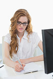 Businesswoman writing document at office desk