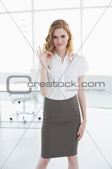 Portrait of young businesswoman gesturing ok sign