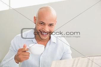 Smiling man having coffee while reading newspaper