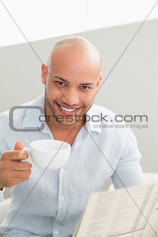 Smiling man having coffee while reading newspaper