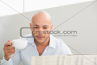 Serious man having coffee while reading newspaper