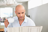 Man having coffee while reading newspaper at home