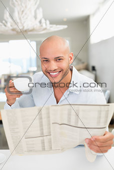 Smiling man with coffee cup reading newspaper at home