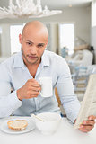 Man drinking coffee while reading newspaper at home