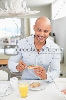 Smiling man having breakfast at home