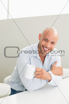 Smiling man holding coffee cup at home