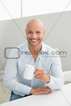 Smiling handsome man holding coffee cup at home