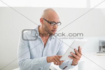 Casual man using digital tablet at home