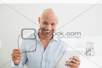 Casual smiling man using digital tablet at home